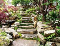 jardin asiatique avec escalier extérieur en pierre naturelle, arbres, plantes vertes et clôture en pierre reconstituée