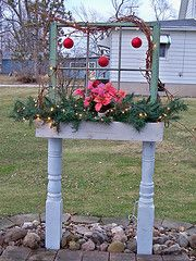 On old window frame, a porch post cut in half and a flowerbox added.  I change the flowers and decorations for the seasons.