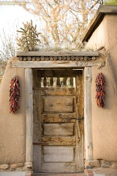 Carved Rustic Santa Fe Door.  See the cross piece over the door and the side pieces, perhaps we could add something similar, either new or found, to your front door to give it character.
