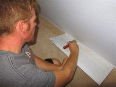 paint baseboards: use cardboard underneath to push down carpet. Painters tape above baseboard(not shown in pic).