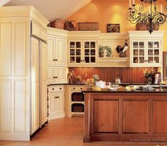 Traditional Antique White Kitchen Cabinets with beadboard backsplash and dark countertops.