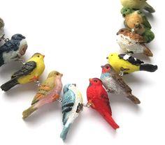 Dit is een van de leukste kettingen die ik heb gedaan, ik hou ervan! Een reeks van hars vogel sit langs de basis van een mooie, leuke ketting. Elke vogel is aangesloten via de lussen van de hand gevormd van sterling zilver, elk een afzonderlijke component, toegestaan aan wiggle & spin. Er zijn 12 vogels totaal, van papegaaien & vinken een prachtige rode kardinaal instellen in het midden. Aan de uiteinden zijn ovale schakels van sterling zilver. Eindigt met een handgemaakte haak clasp, die…