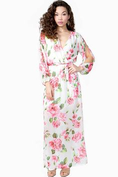 Soft and romantic maxi dress, featuring a pretty pink floral print and long sleeves with an alluring slit detail. Surplice front. Ribbon waist tie.