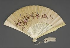 Folding Fan with Box | LACMA Collections Folding Fan with Box China, mid-19th century Costumes; Accessories a) Fan: Silk leaf, bone sticks and guards, metallic loop, mother-of-pearl button, silk tassel a) Fan: Length of guard: 12 in. (30.48 cm); Spread: 19 1/2 in. (49.53 cm) Gift of Anita S. Watson (M.83.189.30a-b) Costume and Textiles Not currently on public view