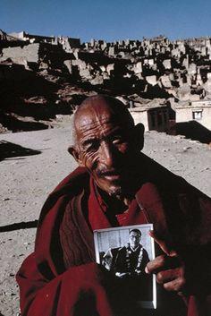 Old monk holding photo of 14th Dalai Lama