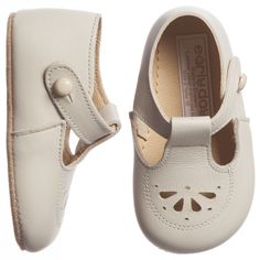Rich ivory, pre-walker shoes by Early Days in a traditional style with a t-bar and little button fastening. Made in England from beautifully soft Italian leather, special attention is given to the shape of the front to provide room for tiny toes. They have a supple sole which moulds to undeveloped feet and on the top is a cute, cut-out petal design.