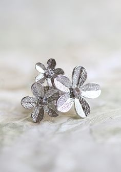 "Silver Flowers Ring 16.99 at shopruche.com. A trio of silver colored blooms accented with sparkling rhinestones is perfected on this ring. Elasticized band.  1.5"" Wide, Adjustable band"
