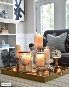 Make a visual statement with a clustered grouping of metal and glass candleholders in varying heights on your coffee table. Coffee Table Styling, Coffee Table Design, Decorating Coffee Tables, Living Room Candles, Table Decor Living Room, Coffee Table Candles, Table Decorations, Trays, Metal