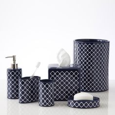 Jill Rosenwald's bath accessory collection adds a polished look to any bathroom. Crafted from durable ceramic, the accessories feature a white geometric pattern over a glossy navy background. Each pie