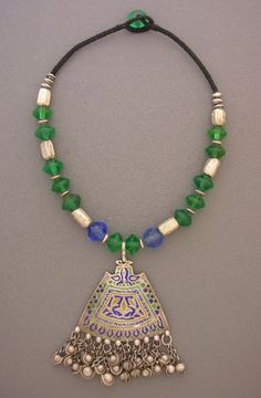 by Anne Holland | A rare old enameled pendant from Pakistan, called a multan, with dangles  in wonderful condition hangs beneath antique blue and green vaseline  beads, large Tuareg silver beads, and some small old silver Ethiopian silver  beads on a hand-braided cord. The button clasp and loop is made from an  antique green vaseline bead. These vaseline beads were most likely  made in Czechoslovakia in the 19th century and traded in Africa. | 525$