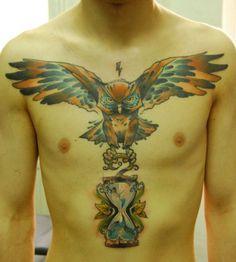 An owl carries an hourglass in this chest piece tattoo by Berlin artist Jukan