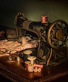 antique sewing machine, fabric, thread, & glasses. beautifully photographed.
