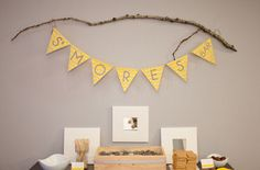 Smores bar at a baby shower with yellow chevron stripes banner displayed on a rustic tree branch