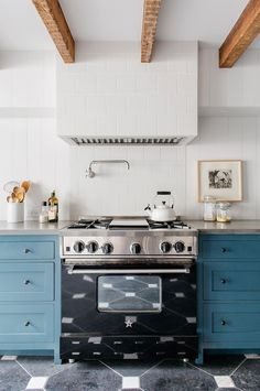 Blue cabinetry in white kitchen with exposed ceiling beams and white teapot