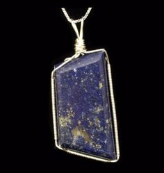 Jewellery By Shalini: Lapis Lazuli pendant wrapped in Sterling silver wire, on a sterling silver box chain.    The Cabochon was cut and polished from rough in-house in our lapidary workshop on our diamond cabochon machine. £60.00