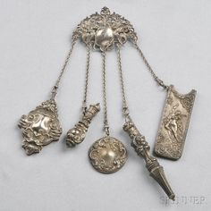 Art Nouveau Sterling Silver Chatelaine, Wm. B. Kerr & Co., the two vials, a comb case depicting Cupid and Psyche, notebook, and mirror all suspended from griffin and scrolling foliate motifs, total lg. 9 in., maker's mark.