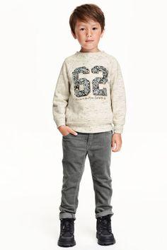 Pantalon en velours côtelé: Pantalon 5 poches en velours de coton côtelé. Élastique réglable à la taille et braguette zippée avec bouton-pression (tailles 134 à 140 avec bouton).