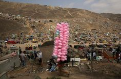 A street vendor sells candy floss as people visit tombs of relatives and friends at the Nueva Esperanza cemetery in Lima, Peru, during the Day of the Dead celebrations