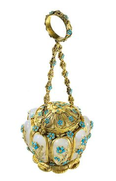 An early 19th century gold, chalcedony and turquoise vinaigrette of Royal interest. Of pumpkin shaped form composed of eight tapering oval cabochon chalcedony panels with applied chased two colour gold flowers with turquoise flowerheads on gold foliate foot, the matching hinged cover with turquoise flowerhead detail and central cartouche set with the Royal cypher for Queen Adelaide (1792-1849) suspended from a fancy link chain and finger ring with turquoise and gold flowerheads, circa 1835.