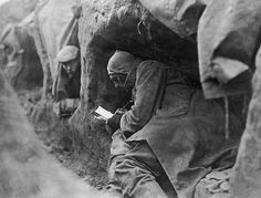 Soldiers in trenches during war time write letters home.