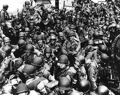 Army troops on board an LCT ready to ride across the English Channel to France. Some of these men wear 4th Infantry Division or 101st Airborne Division insignia 12 June 1944.