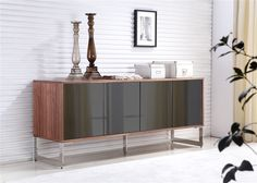 Positioned on stainless steel base, the frame of this modern buffet is finished with walnut wood veneer and completed with mirrored glass fronts.