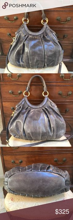 """💯AUTHENTIC MIU MIU SHOULDER BAG Beautifully distressed grey with gold hardware shoulder/ messenger bag. Great condition with purple satin fabric inside. A re Posh only because I haven't used it and a little smaller for what I need it for. The has a distressed look. Please ask any questions the full length is @14"""" x Full height(not straps is @12.5"""" depth 5"""". Handle drop is 9"""" fits right under the arm. The lighting is perfect to show the distressed look of the leather Miu Miu Bags Shoulder…"""