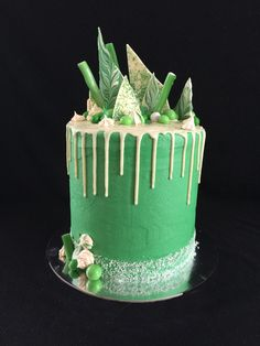 Green and white drip cake, with white chocolate shards, meringues, lollies and m&m's.