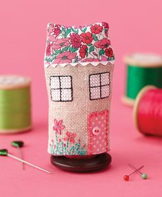 Tiny stitched house from CrossStitcher magazine. Techniques used include cross stitch, embroidered flowers and hand stitching to create the house.