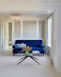 In the master bedroom, a tufted settee upholstered in blue velvet and a glass coffee table lend a boutique hotel vibe.