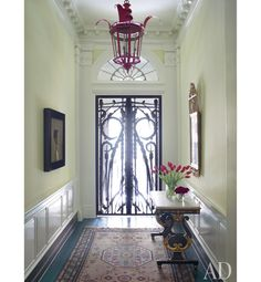 A Charles Edwards lantern adds a splash of color to the entrance hall of a Philadelphia house decorated by Thomas Jayne. Albert Paley sculpted the iron gates, and the Swedish neoclassical table and Danish mirror are from H. M. Luther Antiques