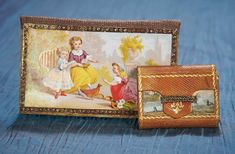 """3 1/2"""" (9 cm.) x 2"""" larger. The larger is of stiff paper stock with embossed paper edging around an image of three children in the garden on one side and geometric design on the other,with marbled paper and wool needle cloths with needles on the interior. Along with a smaller leather bound folio with four scenic engravings,gilt tooling including emblem on flap,and interior designations for four different size needles,Excellent condition. For the French market,early/mid 1800s."""