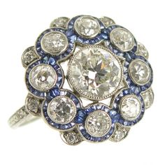 1920s Platinum Diamond and sapphire Ring. Circa 1920s Platinum Ring, centrally set with a .95 carat European cut Diamond and surrounded by another 1.10 carat of European cut Diamonds and Caliber cut Sapphires. The Diamonds are very clean and face up fairly white. The ring is further enhanced with very nice hand Engraving design work. The top of the ring measures 5/8 inch in diameter.