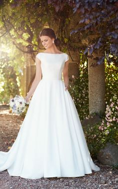 For the timeless, modest bride in search of a timeless, modest wedding dress, this is the one! This Pearl Mikado gown from Essense of Australia features elegant cap sleeves and a boat neckline. The waist is accented beautifully by an attached belt before the gown flows into a full, A-line skirt - complete with pockets! The back of the gown features a sweet low back and zips up beneath fabric buttons. Available in plus sizes.