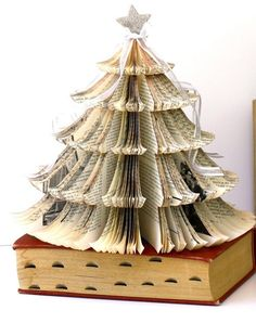 Old Book Christmas Tree. Made from an old book titled Music in Europe and the United States, it's topped with a silver glitter covered star, and white organza with silver cascading bows. The page edges have been stained with a brown paint wash. Book Christmas Tree, Book Tree, All Things Christmas, Christmas Fun, Christmas Decorations, Christmas Ornaments, Holiday Tree, Xmas Trees, Vintage Christmas