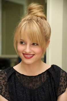 Straight blonde wrapped bun updo with long face framing wispy bangs hairstyle with golden highlights