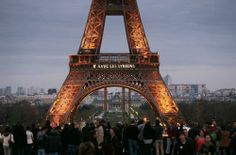 """People gather in front of the Eiffel tower with a projection of the words """"With the Syrians"""", during a demonstration to mark the third anniversary of the Syria's civil war, on March 15, 2014 in Paris. Syrian troops advanced Saturday in the key rebel bastion of Yabrud as the country's civil war entered its fourth year, with more than 146,000 dead, millions displaced and peace efforts stalled."""