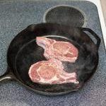 Using oven mitts, carefully remove the hot skillet from the oven and set it over medium-high heat on the stovetop. Lay the pork chops in the hot skillet. You should hear them immediately begin to sizzle. Sear until the undersides of the chops are seared golden, 3 minutes.