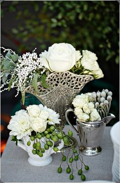 white flowers and silver vases