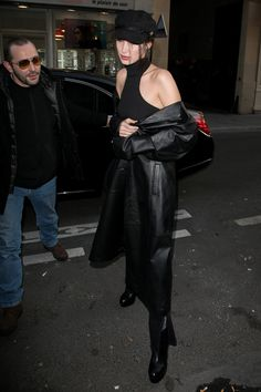 Bella Hadid chose a flat cap, black top and leather trench-coat for another outing in Paris.