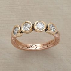 """Round diamonds are brilliant counterpoints to Jes MaHarry's rustic setting. 14kt yellow gold bezels spell """"love"""""""