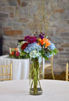 Tall centerpiece of colorful flowers. Blue hydrangea, orange lily, mums, gerbera daisy, and stock. www.larkfloral.com