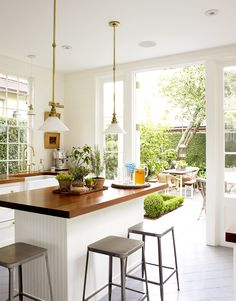 Bright and white kitchen with wood table top and open door