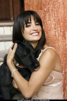 Actress Penélope Cruz getting some love from her chocolate lab