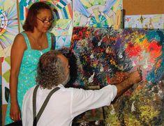 A fotografia exibe uma mulher, um homem e algumas pinturas. A mulher está em pé, na lateral esquerda da imagem, olhando para o homem, que está sentado, de costas, pintando, com a mão direita, em uma tela já bastante colorida. Atrás dela estão expostos alguns quadros com muitas cores.