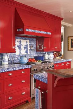 Bright red kitchen cabinets with blue and white patterned tile backsplash and countertops