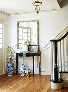 In the foyer, traditional blue-and-white ginger jarsand a shapely brass pendant complement a lacquered console by Oomph.