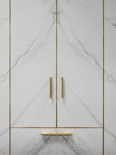 The large freestanding cupboards shown here have been clad in 'book-matched marble' porcelain and edged with brass strips, a feat of craftsmanship in itself. Linear brass handles used across all the cabinetry pick up the metallic gleam, uniting fitted and freestanding elements.