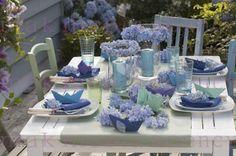 Maritime Hortensien - Tischdeko: Blüten von Hydrangea 'Endless Summer' ( Hortensien ) als Kerzenkränze um Windlichter, Serviettendeko und lose auf dem Tisch, gefaltete Papierschiffchen , Tischde