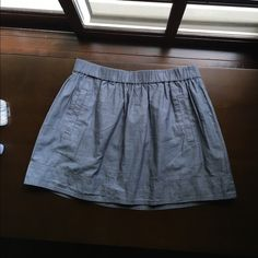 J. Crew Chambray Skirt Classic and polished skirt that can be worn around hips or as a high waisted skirt. Stretchy waistband so even though size is XS would also fit S or maybe M. Lightweight and lined. Worn once. J. Crew Skirts Circle & Skater